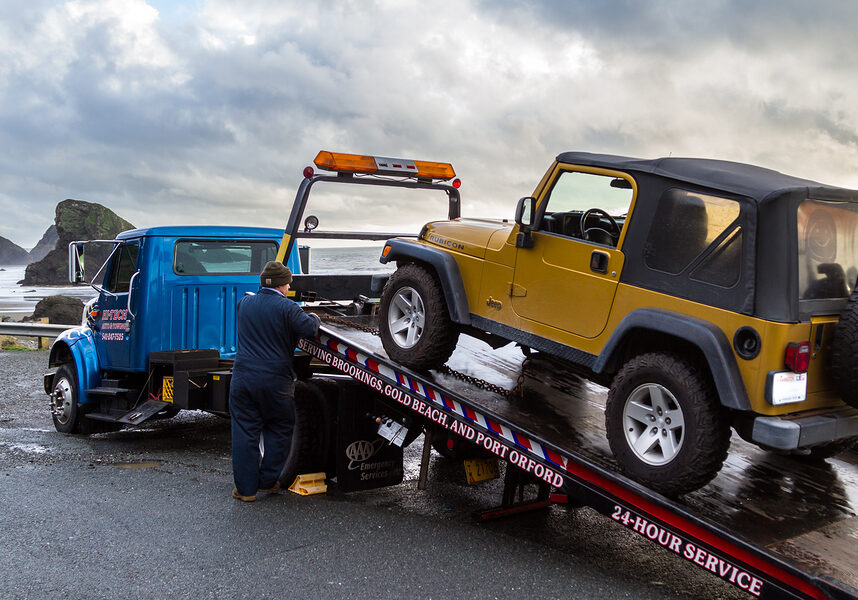 Flat bed tow truck loading a broken vehicle