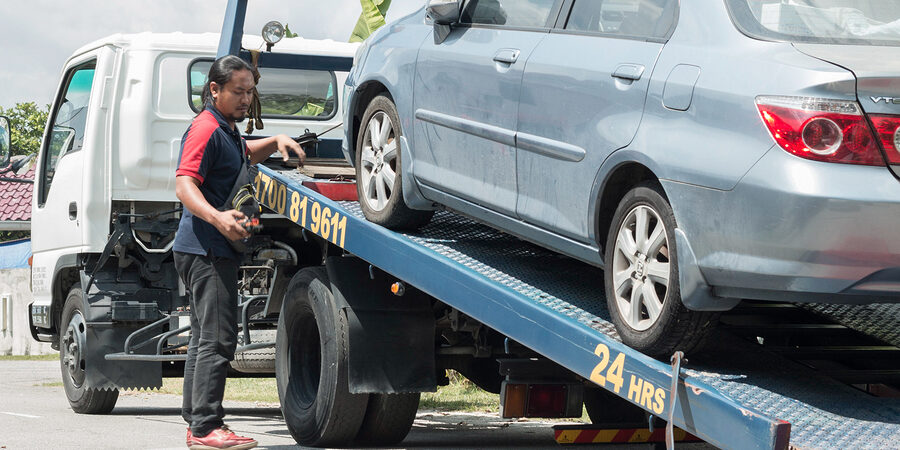 A car has broken down and being pulled up into the tow truck