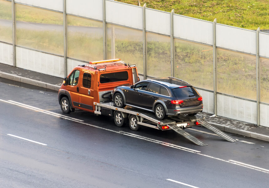Car is transported on an evacuation tow truck on the highway